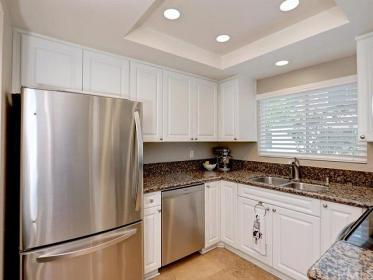 The upgraded kitchen includes white cabinets, recessed lighting in a tray ceiling, granite counters, stainless steel appliances, and tile flooring.