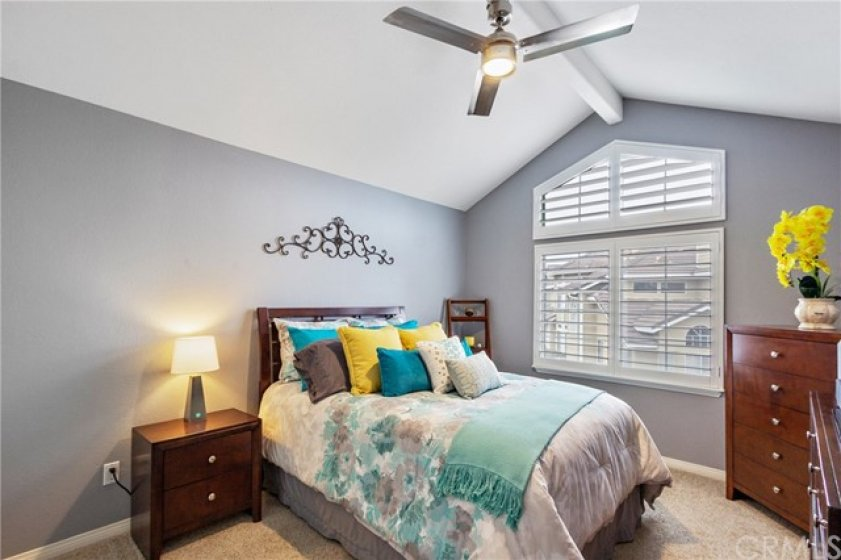 High cathedral ceiling and a lighted ceiling fan create a feeling of space in this bedroom. Warm, plush carpet and a calming paint schema make this a perfect place to wind down for a good nights sleep!