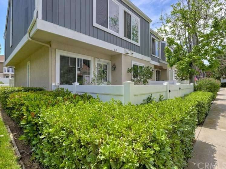 As you approach, you will notice the well sculpted hedges and vinyl fencing that ring the home.