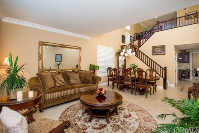 OPEN FLOOR PLAN WITH HIGH CEILINGS FORMAL LIVING/DINING AREA. BOTH OF THE ROOMS HAVE CROWN MOULDING AND PLANTATION SHUTTERS