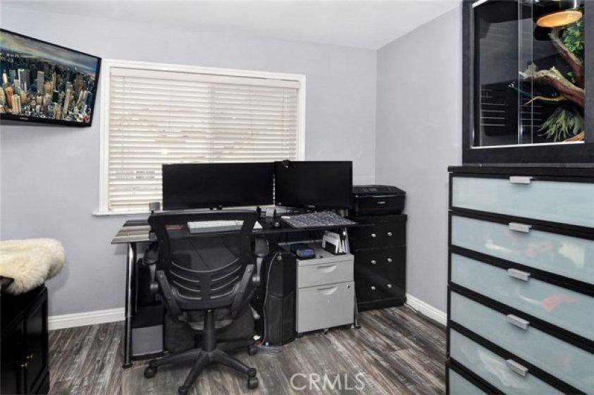 Secondary bedroom, laminate flooring, natural light.
