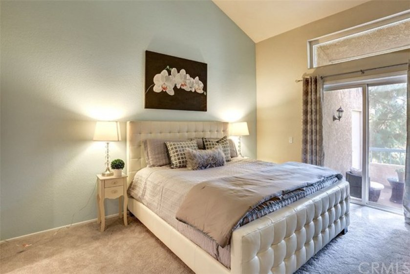 Spacious master bedroom with high ceiling and view of the golf course
