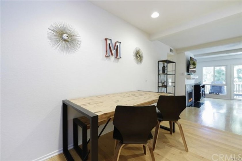 Raised dining area with recessed lighting, opens to the well lit living area.