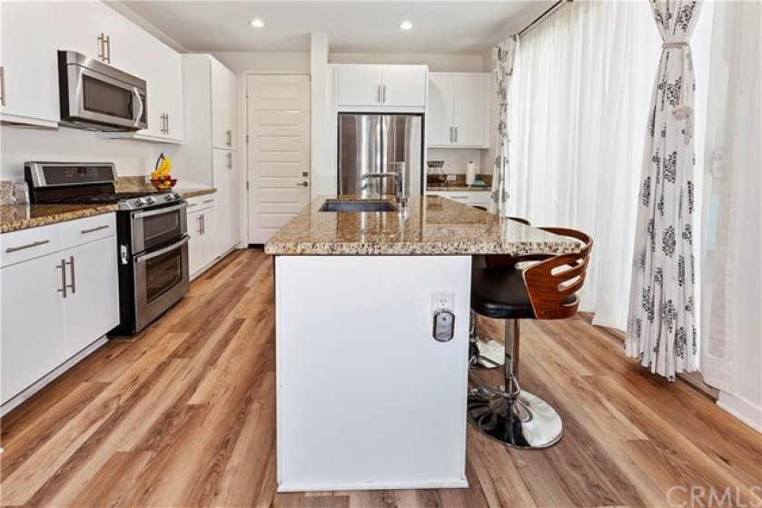 Garage access at left rear of the photo. White cabinets and recessed lights add to the bright kitchen.