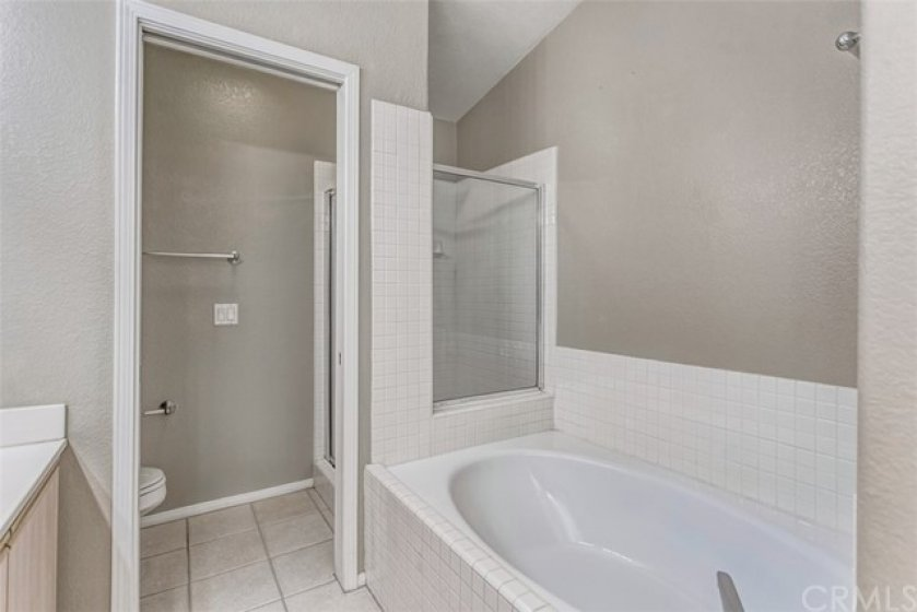 Master bathroom soaking tub which is in front of the walk in shower. There is a door leading into the toilet room.