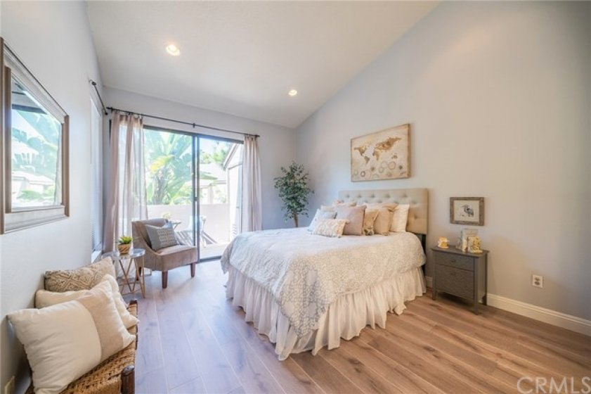 Master bedroom has vaulted ceilings, recessed lighting, and sliding glass door to balcony