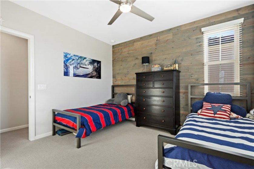 Custom shiplap wall and ceiling fan in bedroom 2.