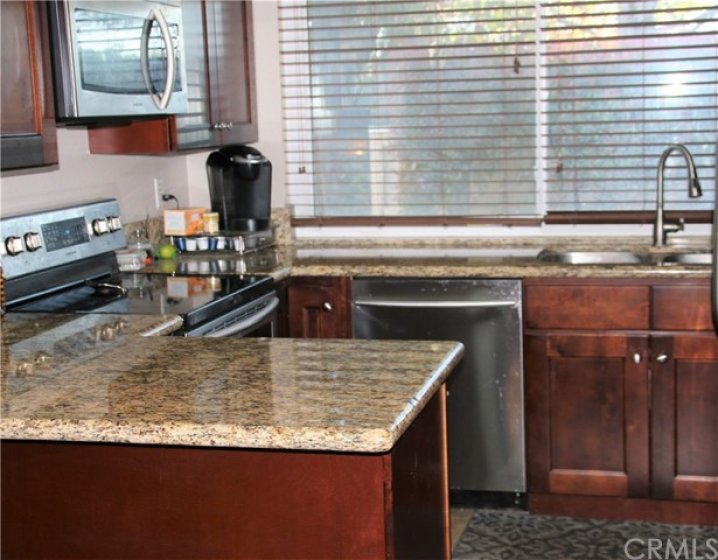 Updated kitchen with granite counters, stainless appliances, tile flooring.