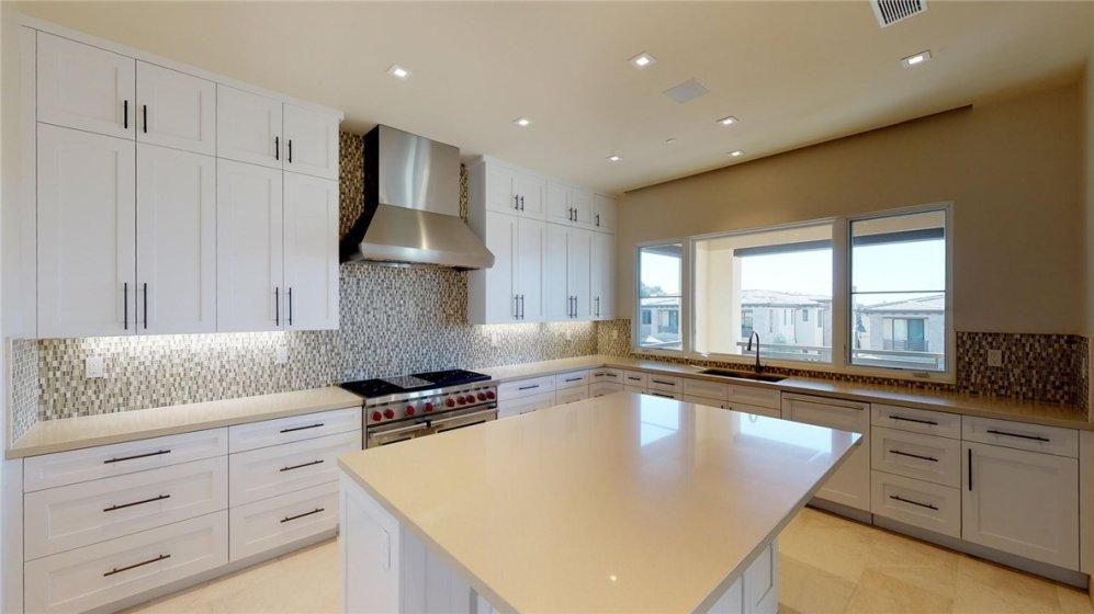 Full decorative tile back splash, stainless steel vent hood and large windows at kitchen sink.