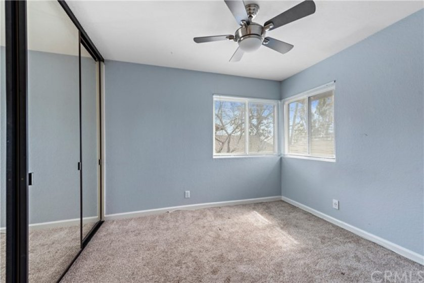 Secondary bedroom complete with ceiling fan and wall to wall mirrored closets.