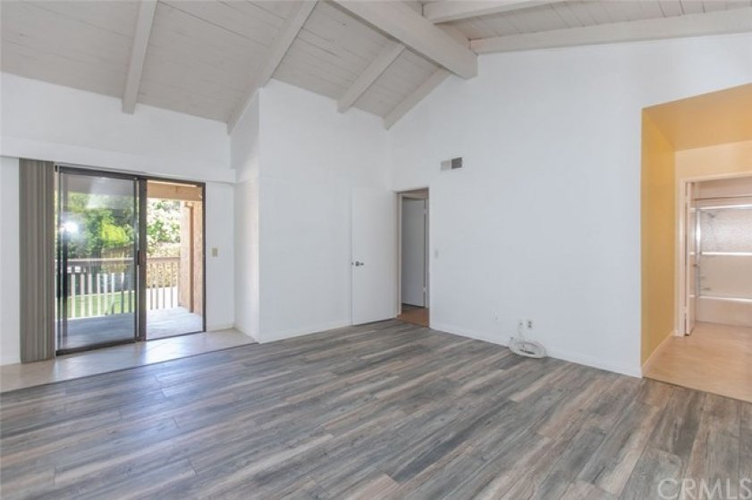 Master bedroom with balcony and new flooring.
