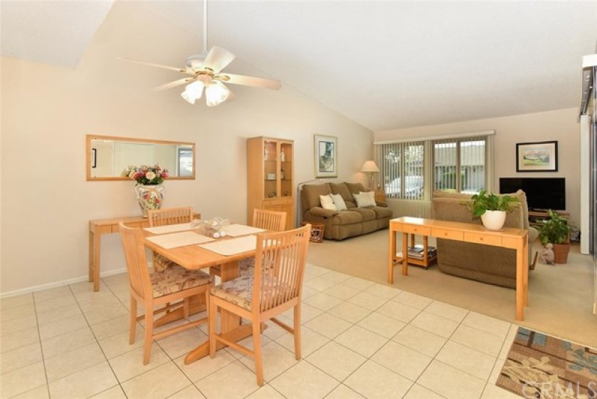 Dining area opens to the living room which features vaulted ceilings & large windows.