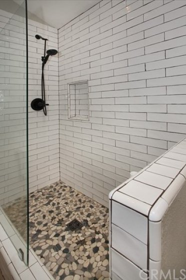 Pebble flooring and organic subway tile shower with a frameless glass shower panel.
