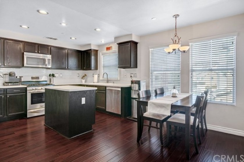Kitchen with stainless steel appliances, quartz countertops and beautiful glass tile backsplash.