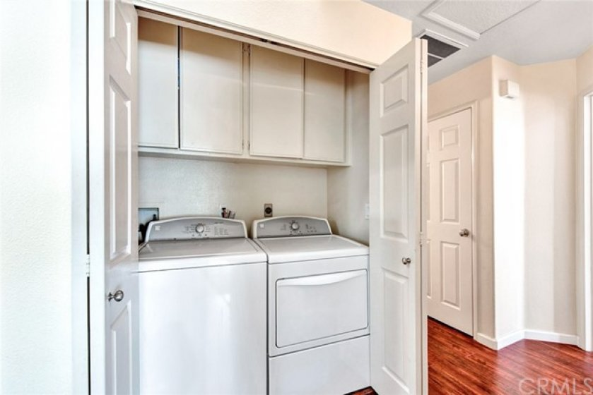 The laundry closets has storage cabinets and has room for a full size washer and dryer.  The door to the right is the coat closet.