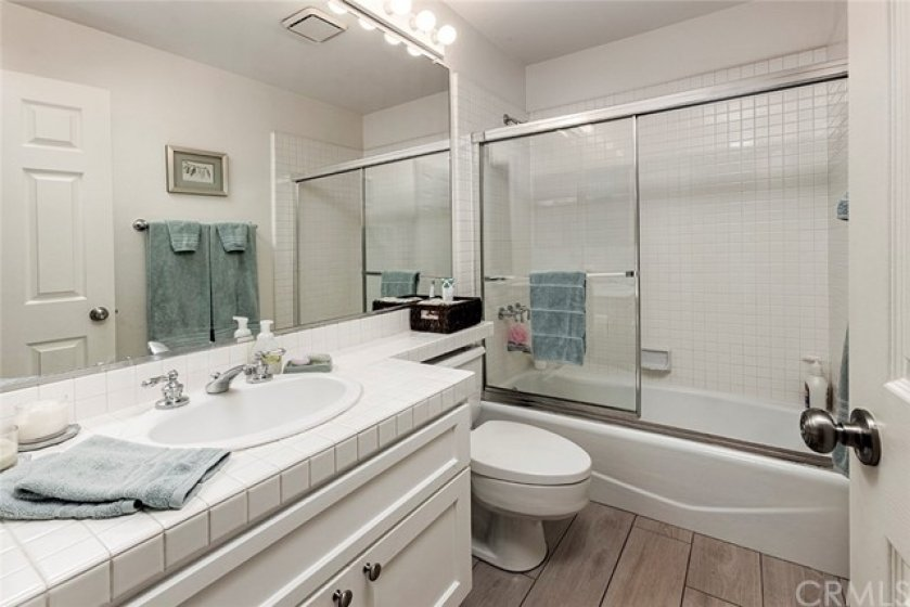 The secondary bathroom has updated tile floors, and freshly painted cabinets.