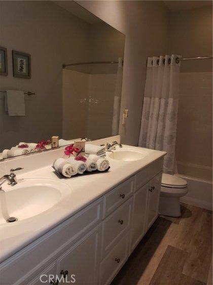 Hall/guest bath 2nd floor - dual sinks, shower over tub - clean, clean, clean!  Same LVP flooring easy clean, smooth under bare feet...