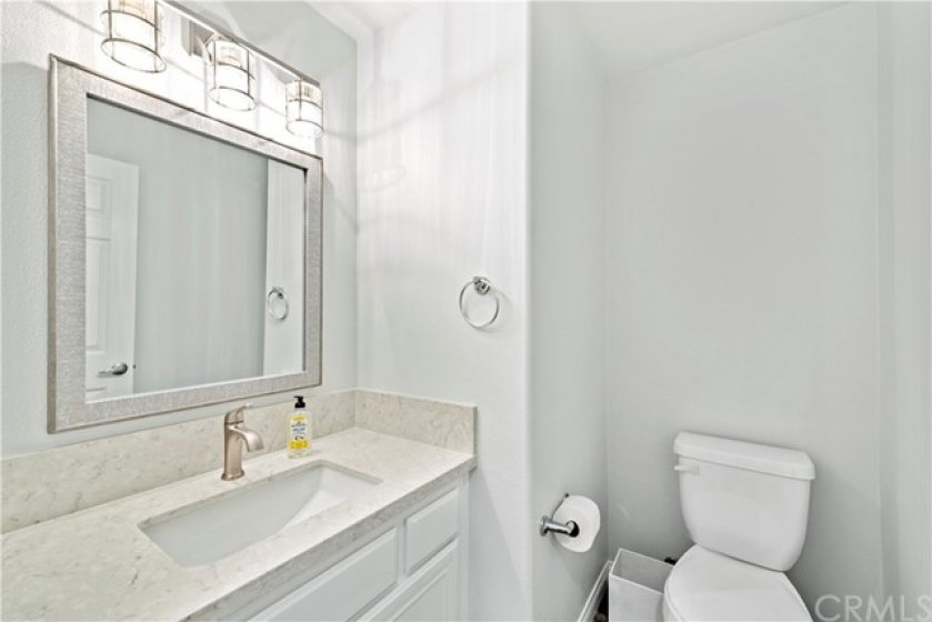 Upgraded downstairs bathroom with new Quartz counters, designer mirror and lighting.