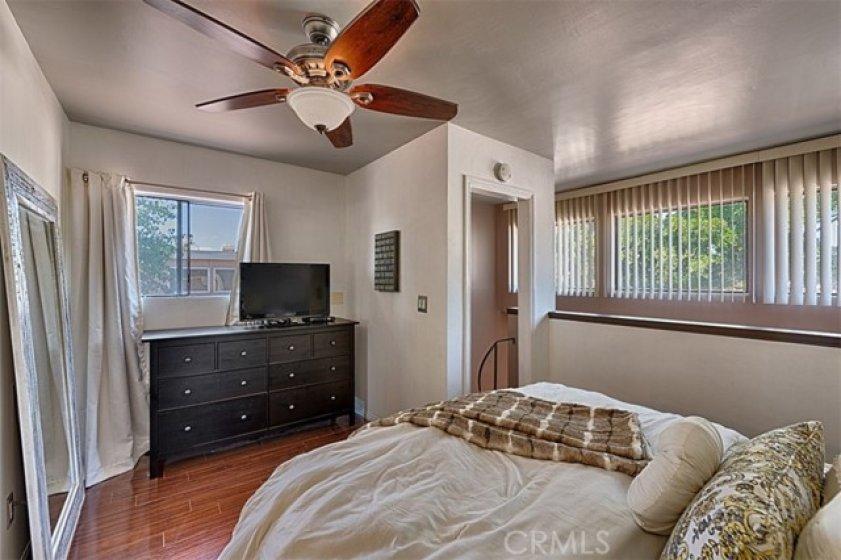 Upstairs bedroom has hardwood laminated flooring.