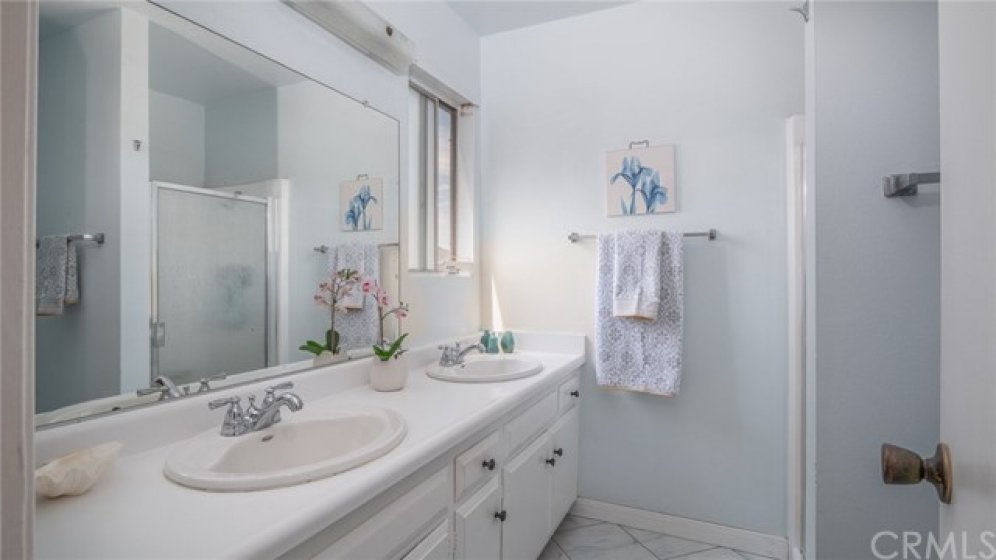 The master bathroom has double sinks and a shower with a breeze coming from the window.