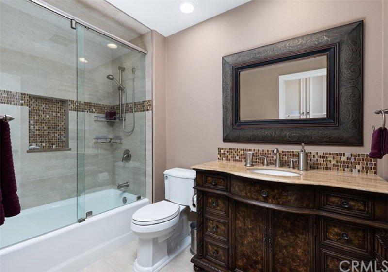 Second bathroom with glass tile details and frameless shower sliding door.