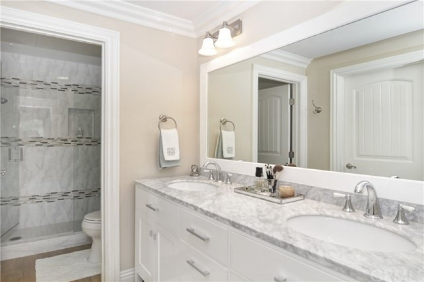 Dual sink master vanity with stone tops and custom large shower with seat.