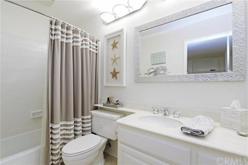 The guest bathroom is located off the hallway. This simple but well appointed bathroom has tile flooring, a tub/shower, single sink vanity with storage below, a decorative mirror and lighting.
