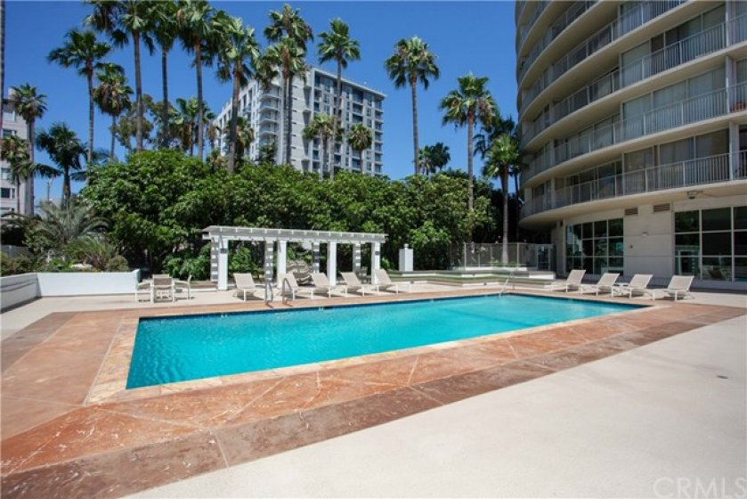9' deep heated Pool protected by glass wind walls, ample lounge furniture and tropical landscaping