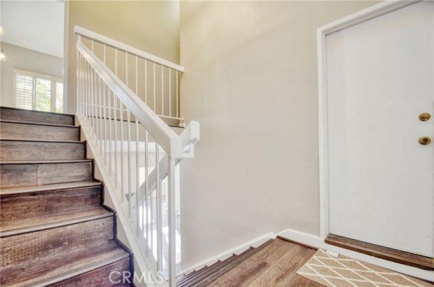 View when walking in through front door. Stairs going up is to split level and stairs going down is to living room. Side door is door to garage.