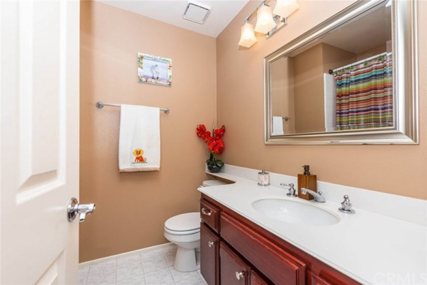 Guest bath offers upgraded lighting, tile flooring, rich wood cabinetry, and full tub.