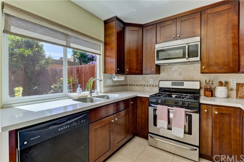 Remodeled kitchen with updated cabinetry, quartz counters, tasteful backsplash and gas range