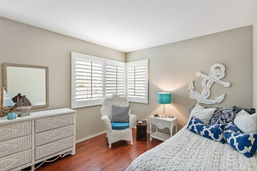 Bedroom No. 1 with laminate flooring, plantation shutters, and new paint.
