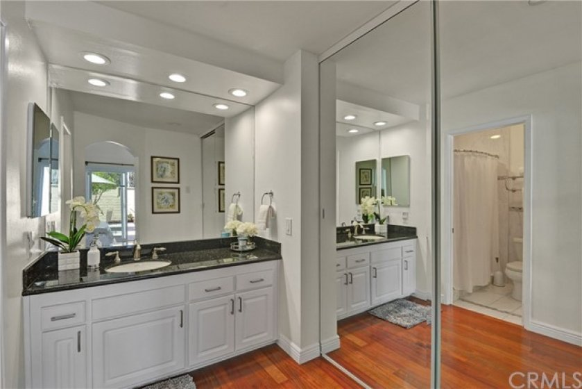Master bathroom has recessed lighting, granite counters and mirrored closet doors.