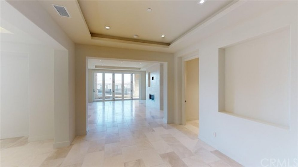 View at the top of the stairs looking toward great room with dining room to the left and master entry to the right.