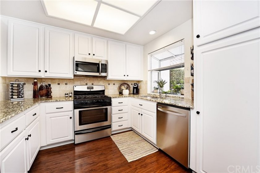 Beautifully updated kitchen with granite, pull outs, resurfaced cabinets and stainless appliances.