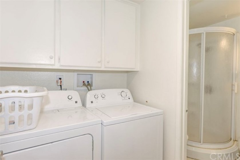 Separate laundry room with storage.