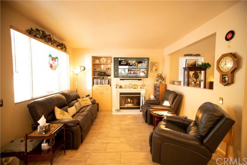 Family room opens to kitchen and warmed by fireplace.