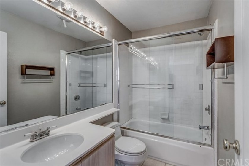The upstairs guest bathroom features a shower tub combo.