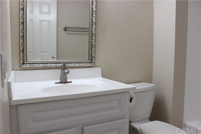 Enjoy the NEWNESS of the bathroom's new sink, cabinet, plumbing fixture, framed mirror and toilet.