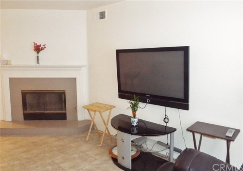 Living room with tile floors and raised hearth tile fireplace.