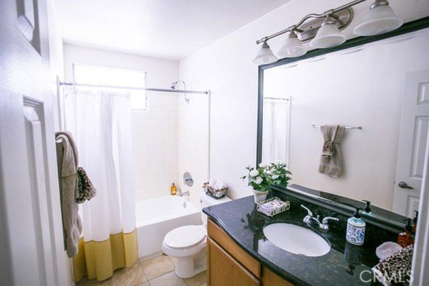 Decorative bath vanity, granite counter, tub/shower combination and tile floors.