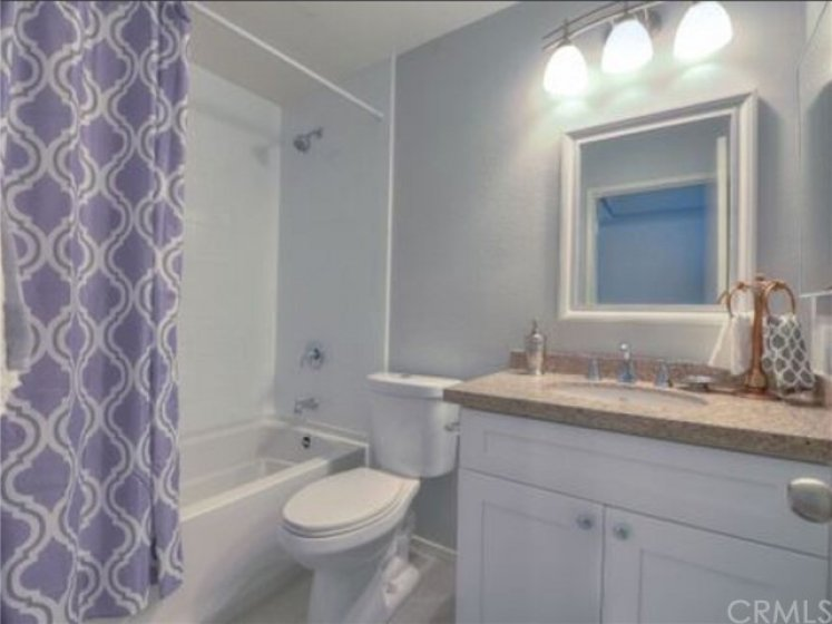 Upstairs bathroom with new tub, toilet, cabinet, tile floor.