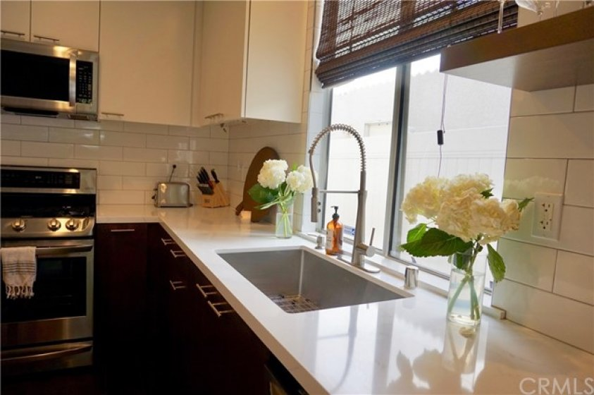 Microwave, oven, stove and white quartz counters make for a gleaming, gorgeous kitchen with plenty of workspace for cooking!