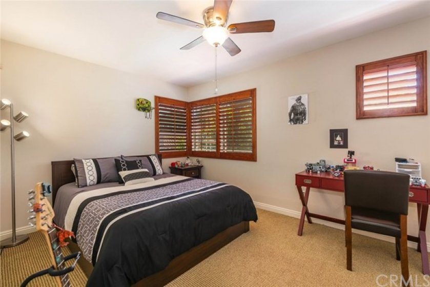 Large secondary room features plantation shutters, upgraded ceiling fan, upgraded baseboards, newer window, and neutral decor.