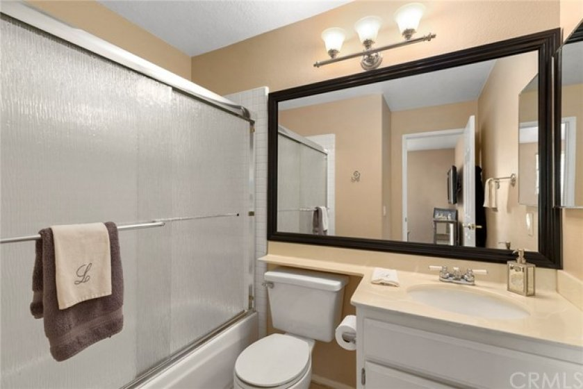 Secondary bathroom in upstairs Guest bedroom- Glass doors for shower over tub- Tile flooring-