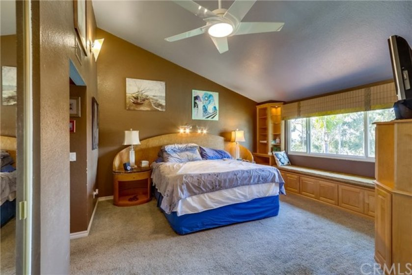 Relax in the master suite featuring two closets, built-ins, and a bay window with tennis court views.