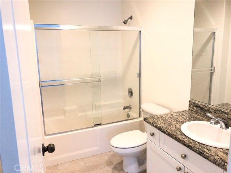 Master bathroom has granite counters and tile flooring.