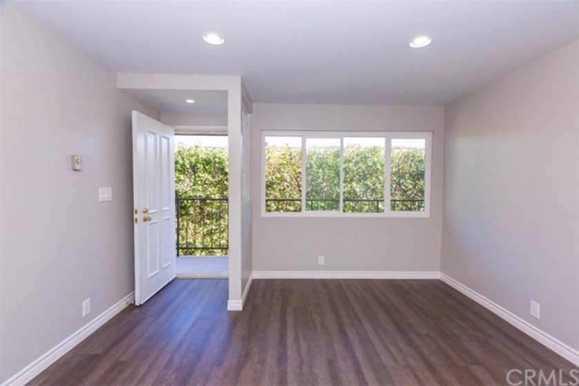 Large, Light/Bright Living Room with new floors, smooth ceilings and recessed lighting.