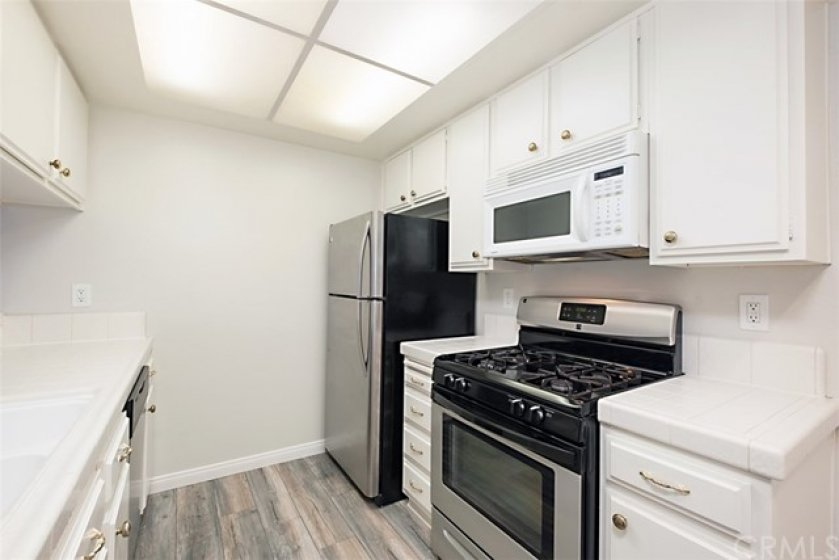 The Kitchen has new Flooring and a Stainless Steel Refrigerator and Stove