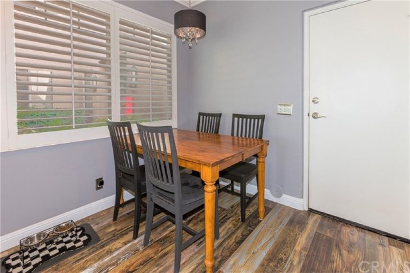 Eat-in kitchen with chandelier, plantation shutters to front courtyard with European flower boxes with newer dual pane windows.